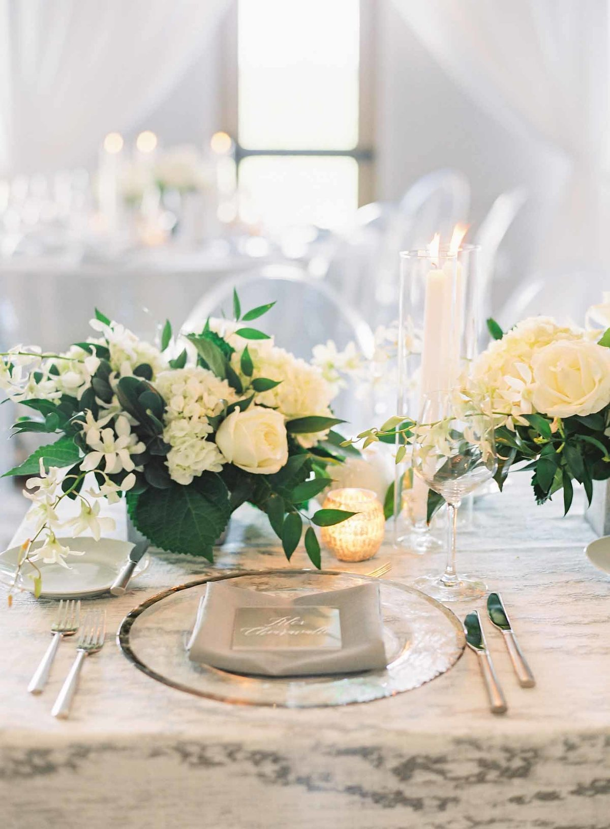 Grey marbled linens look stunning with these white and green floral arrangements with white orchids.