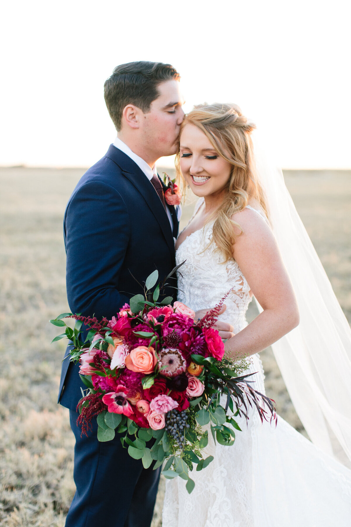 Bride and groom with purple and hot pink bouquet