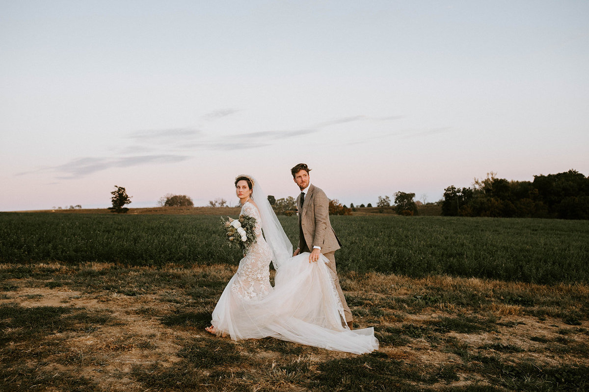 A bride and groom walking away in a field.