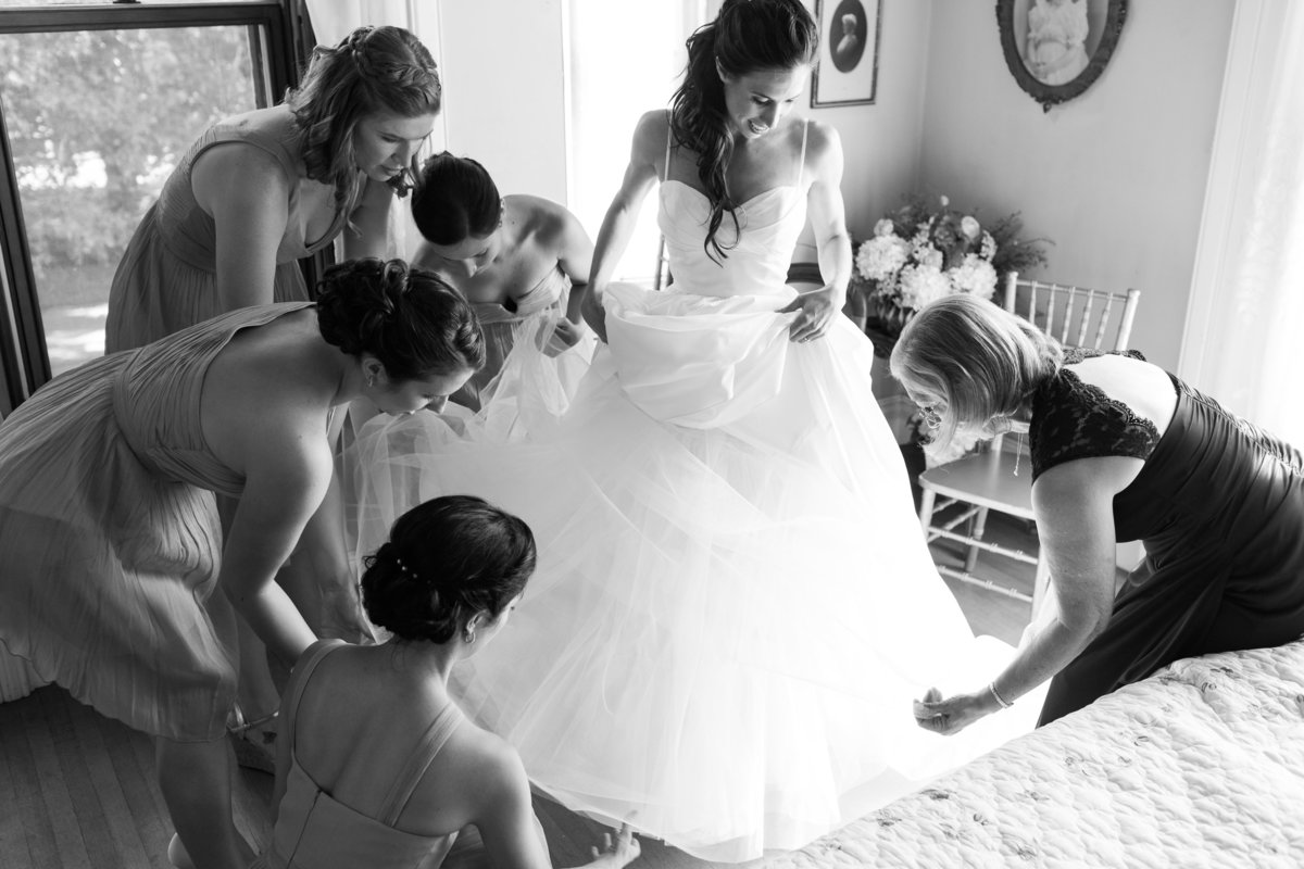 The bride gets the layers of tulle settled on her wedding day at Kimball Jenkins Estate in New Hampshire