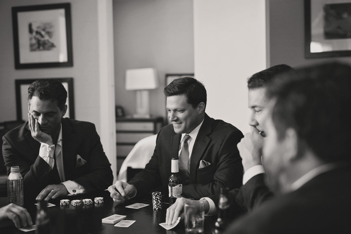 black and white photo journalist photography groom and groomsman playing poker at the Detroit Athletic Club, Michigan, photographer Charlene Gurney