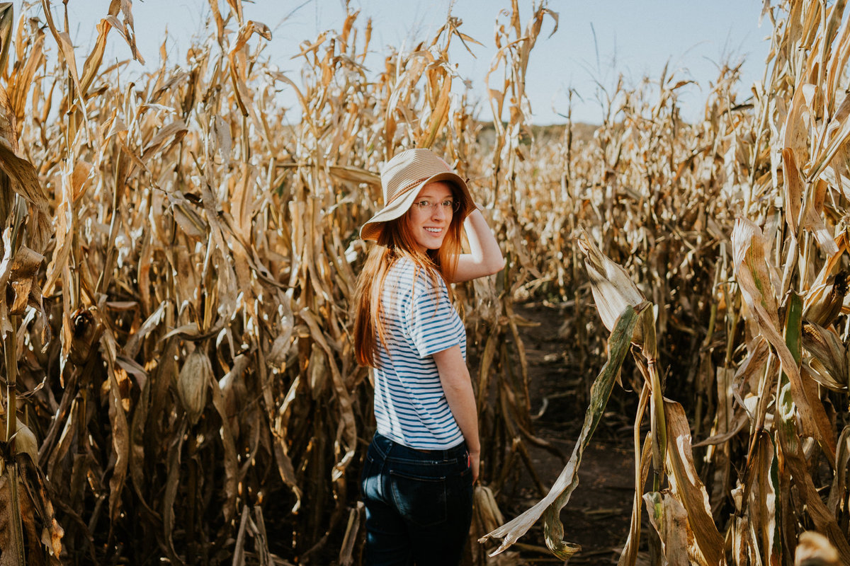 Alexandria wears straw hat and looks back at camera walking through a golden corn maze at Center Grove Orchard in Iowa