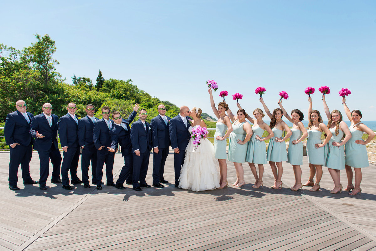 photo of bridal party with bride and groom kissing from wedding reception at Pavilion at Sunken Meadow