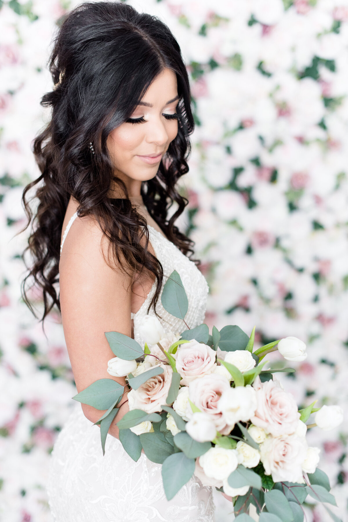 A bride poses in her Galia Lahav dress. She is holding a pink rose and white tulip bouquet from Thuja Floral Design while standing in front of a soft floral wall from Luxy Chair