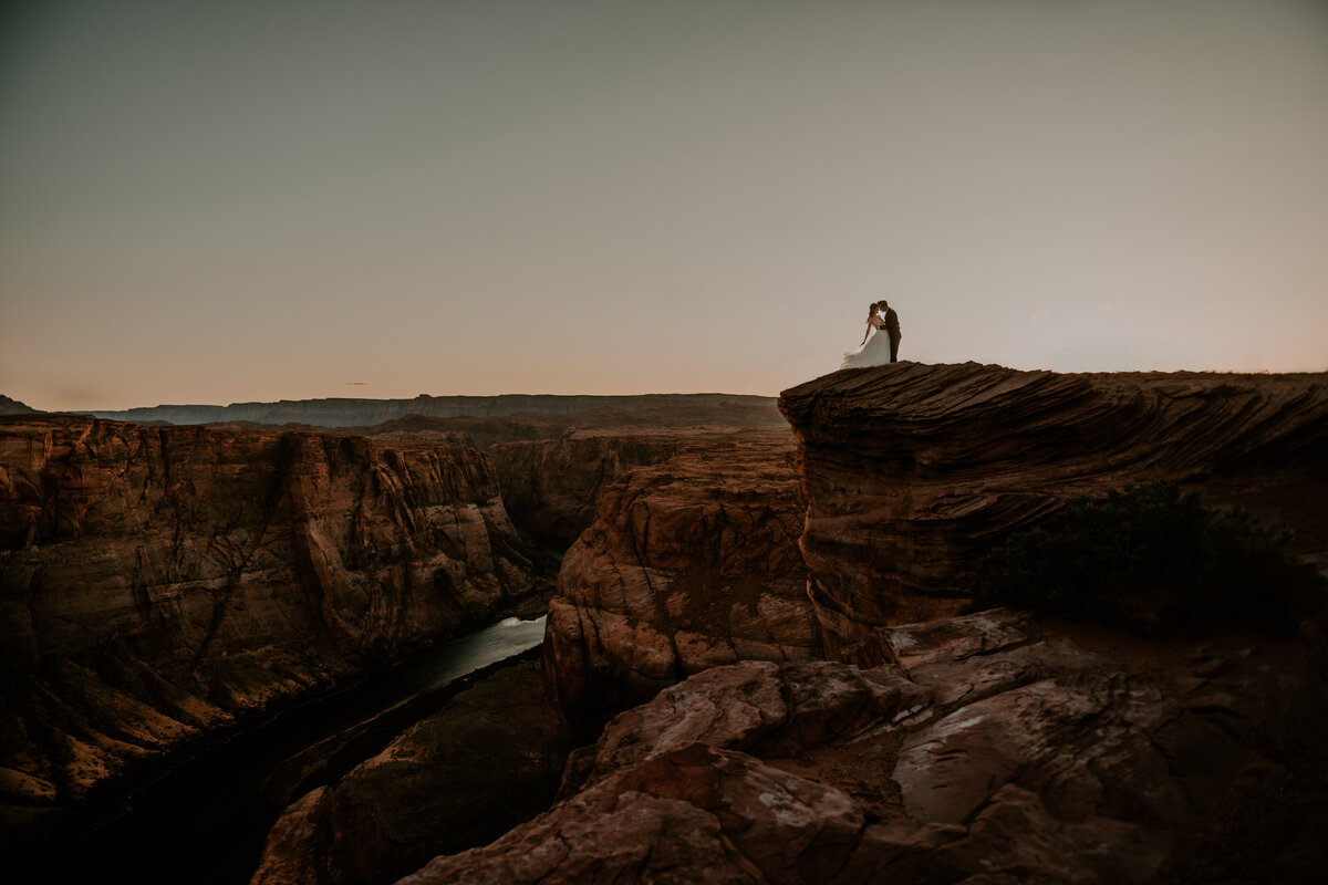bride and groom kissing on a mountain top