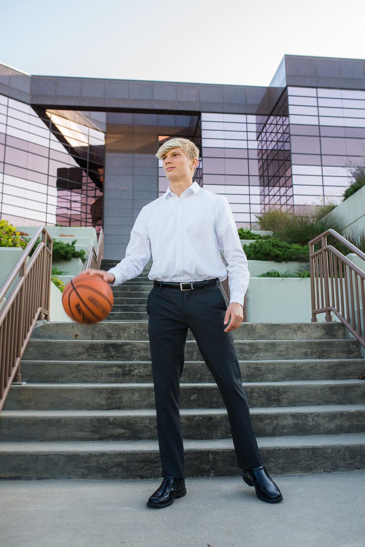 Senior Session Guy in suite and tie with basketball in city