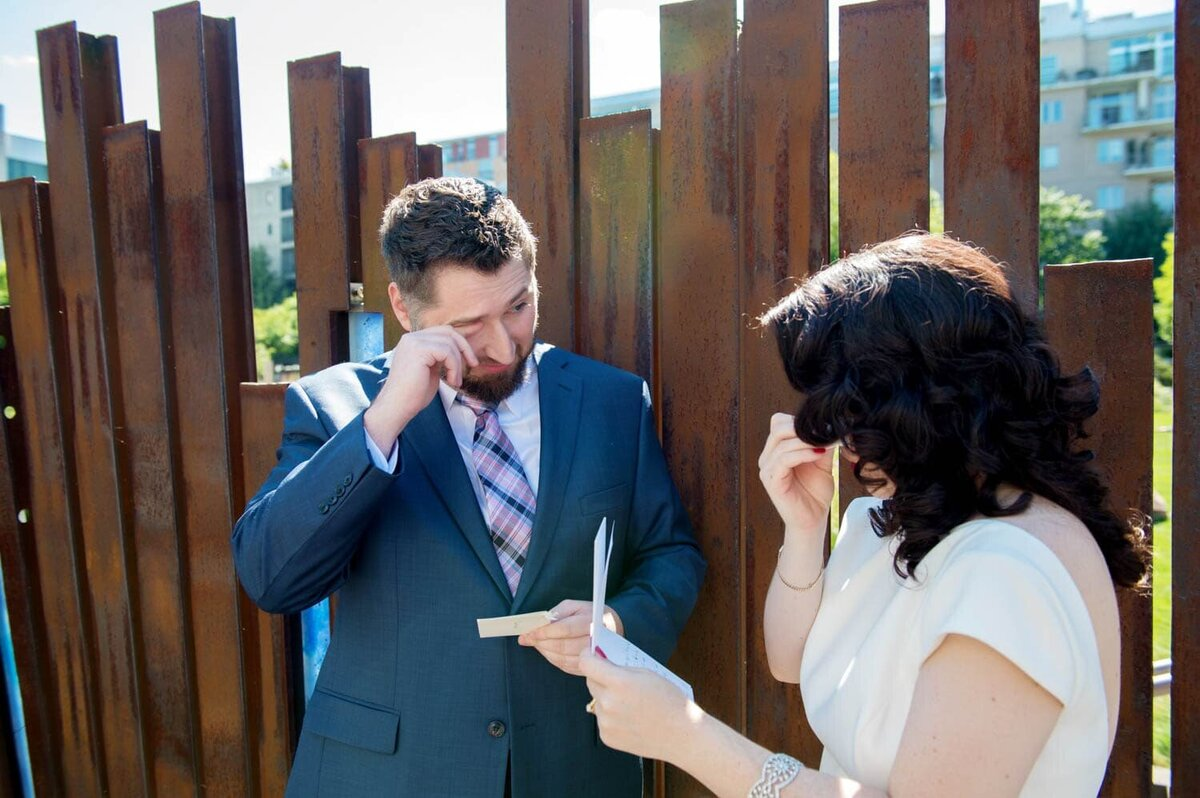 a bride and groom both wipe tears away as they read letters from each other