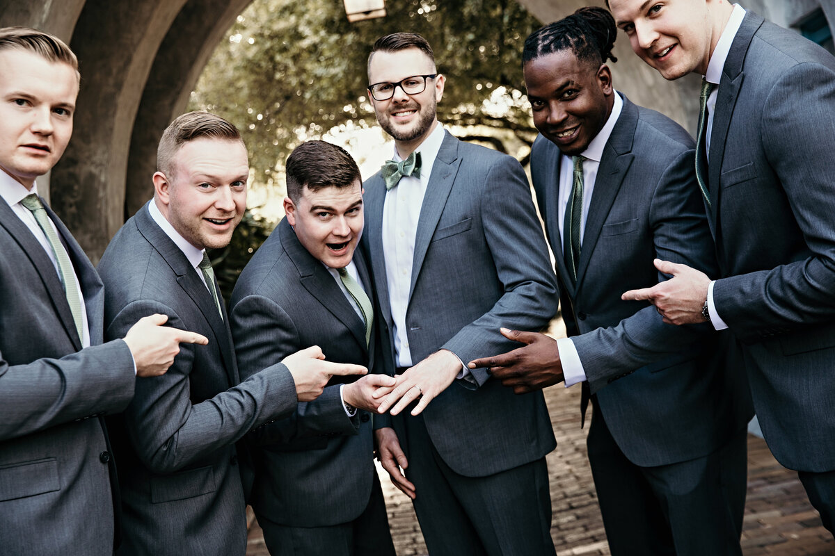 An image of the groom surrounded by his groomsmen who are smiling and pointing to his hand as he now wears a wedding ring by Garry & Stacy Photography Co - St Petersburg FL wedding photographers