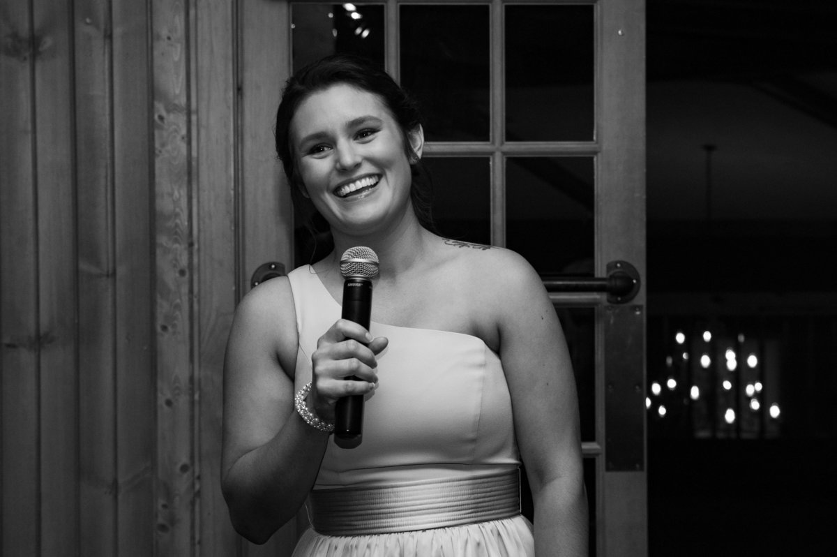 maid of honor toast holding microphone black and white