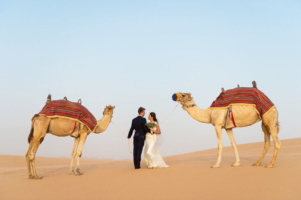 Portrait of the bride and groom with two camels for a photoshoot in Dubai  organized by Lovely & Planned