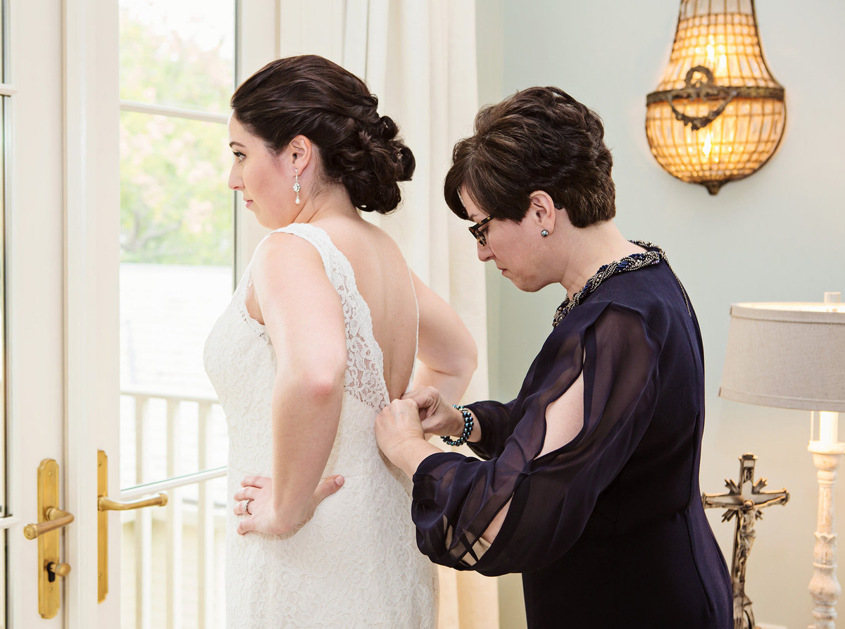 mom helping new orleans bride into wedding dress