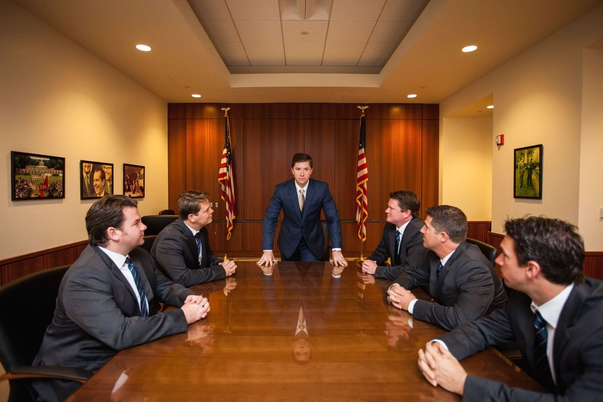 Groom and his Groomsmen having fun posing for a presidential meeting before the wedding