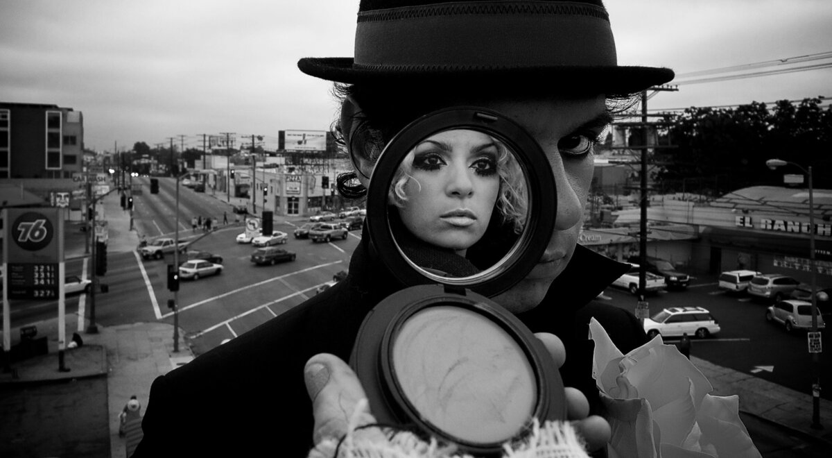 Music Duo Portrait Menage male band member standing on rooftop wearing hat makeup compact covering one side of his face image of female band member in reflection of mirror black and white