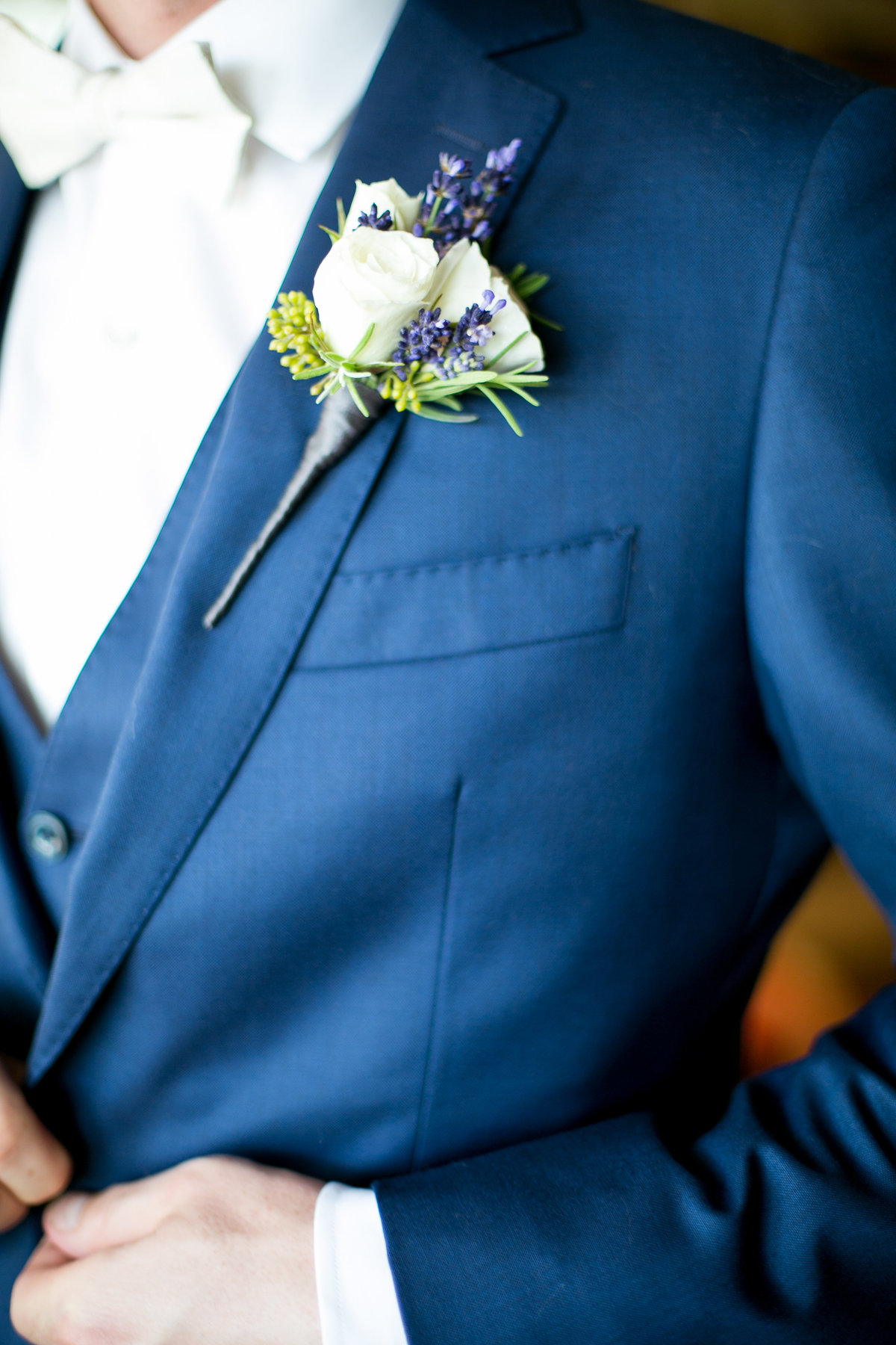 Photo of groom's  boutonniere on a navy suit