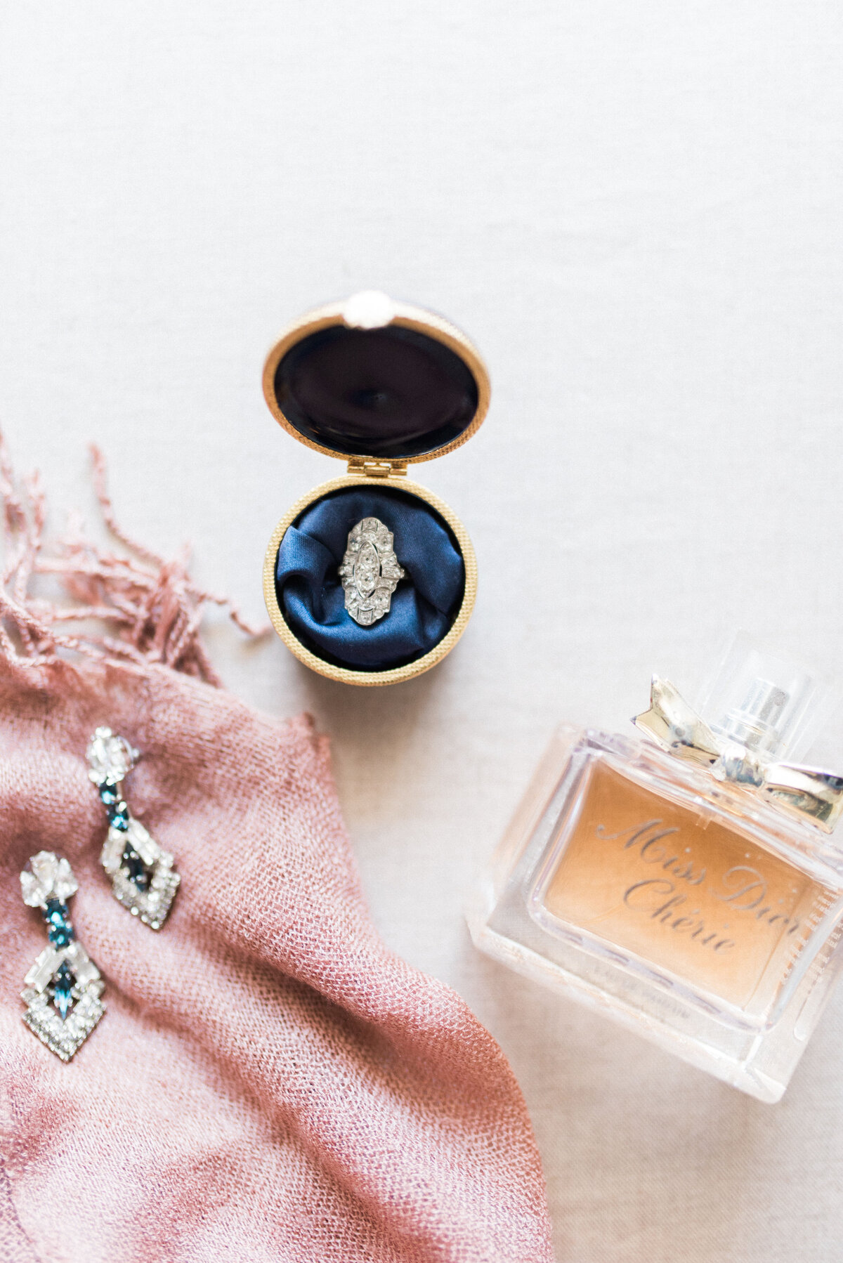 Beautiful wedding ring, heirloom earrings, and perfume worn on wedding day