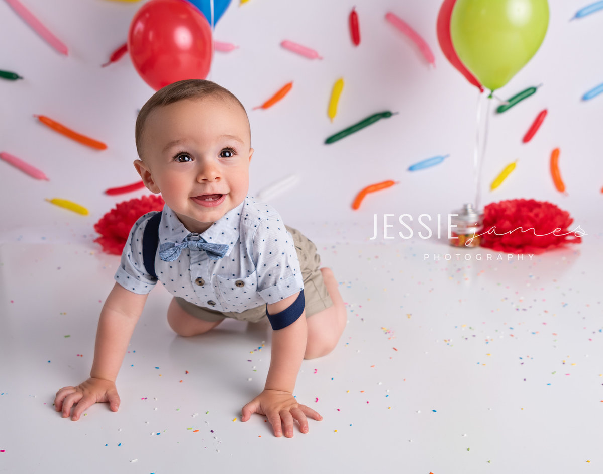 baby boy posing in front of a sprinkles backdrop for ice cream photo session
