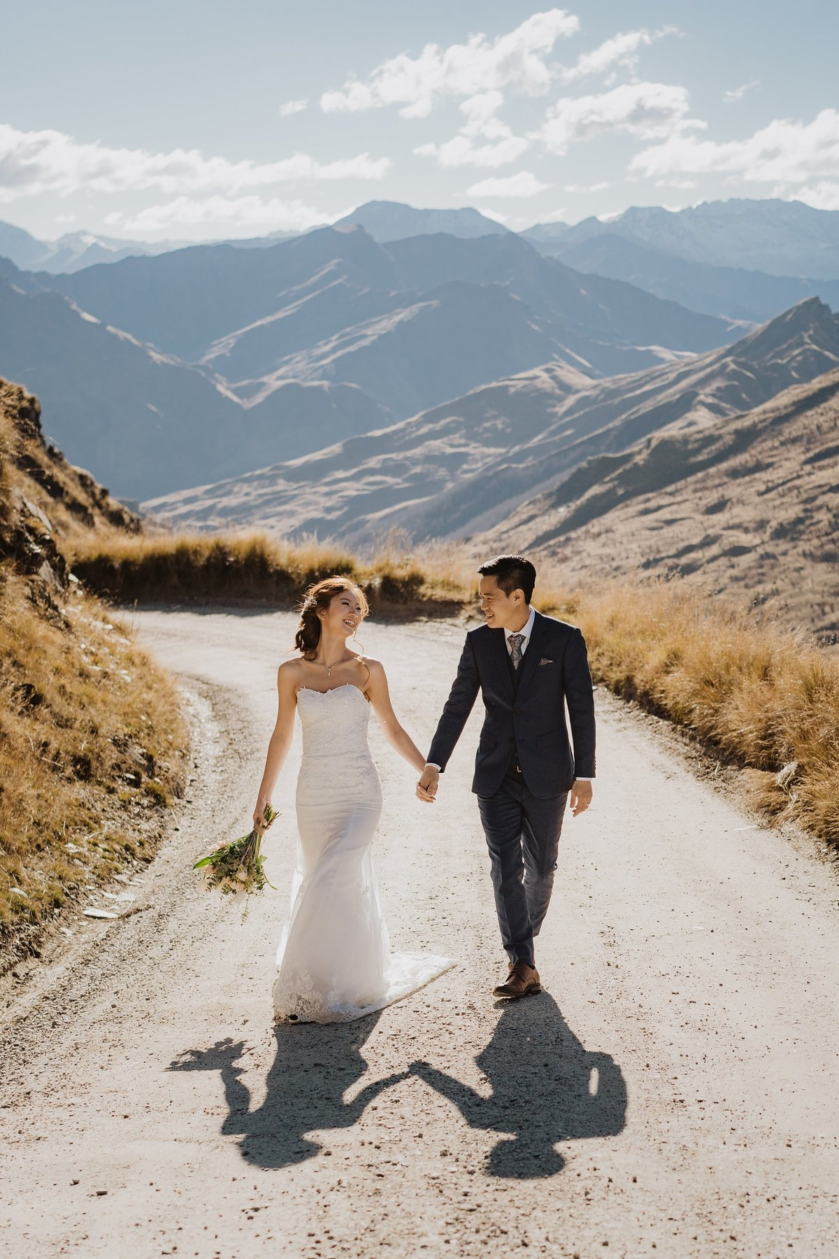 Bride and groom walking down a dirt road in the mountains