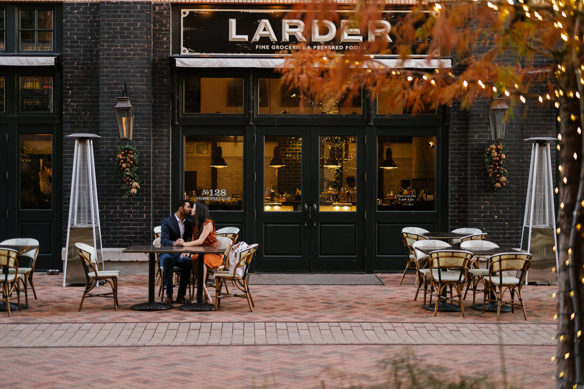 Couple sitting in front of Larder at the Historic Pearl on their engagement session.