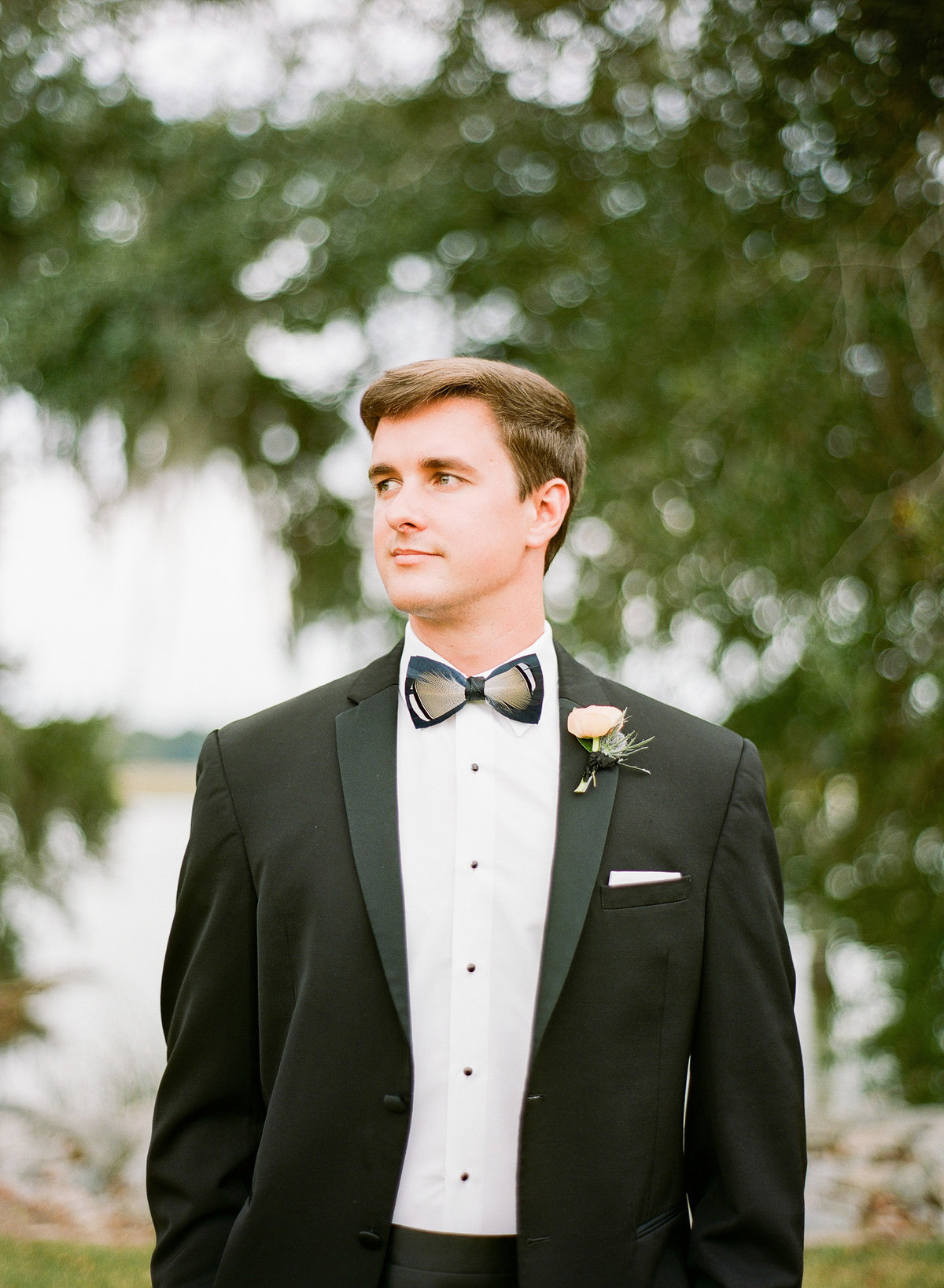 Groom in Black Tuxedo with Feather Brackish Bow Tie Southern Wedding