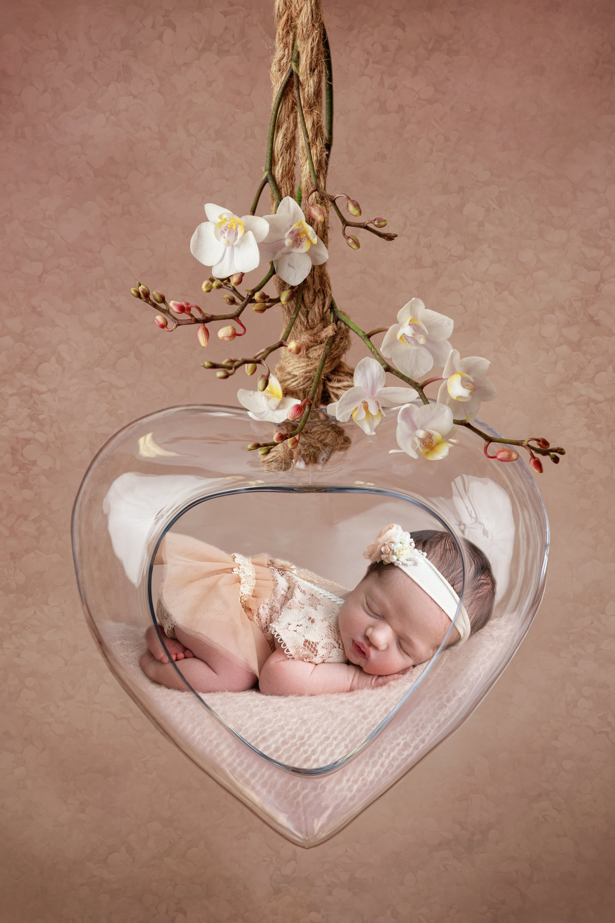 Baby girl lying in a glass heart