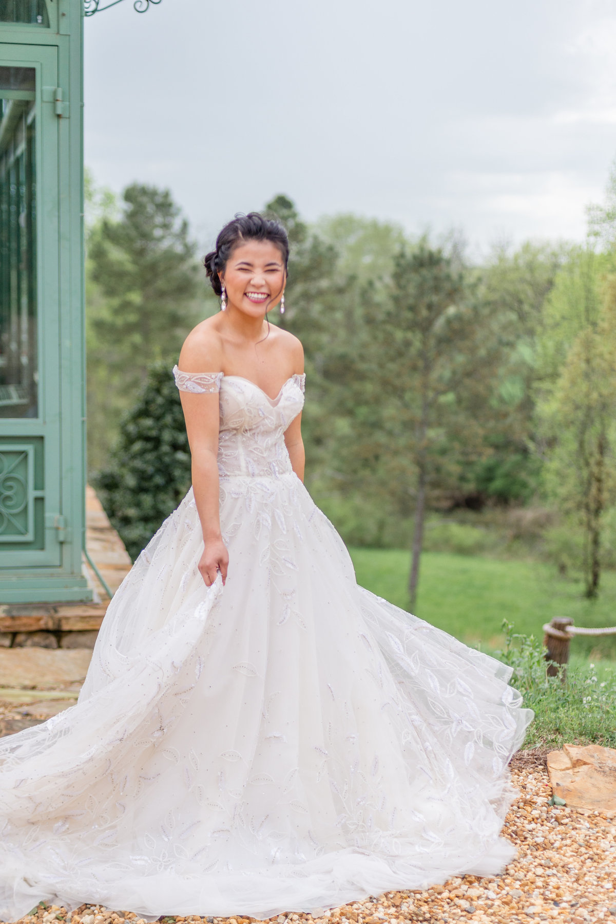 A petite bride twirls her wedding dress while laughing next to a greenhouse in Georgia