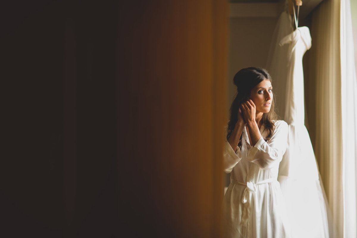 a bride putting her earings in at the grove hotel in london