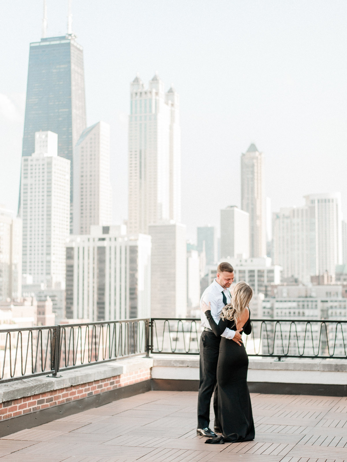 engaged couple dancing on rooftop with chicago skyline
