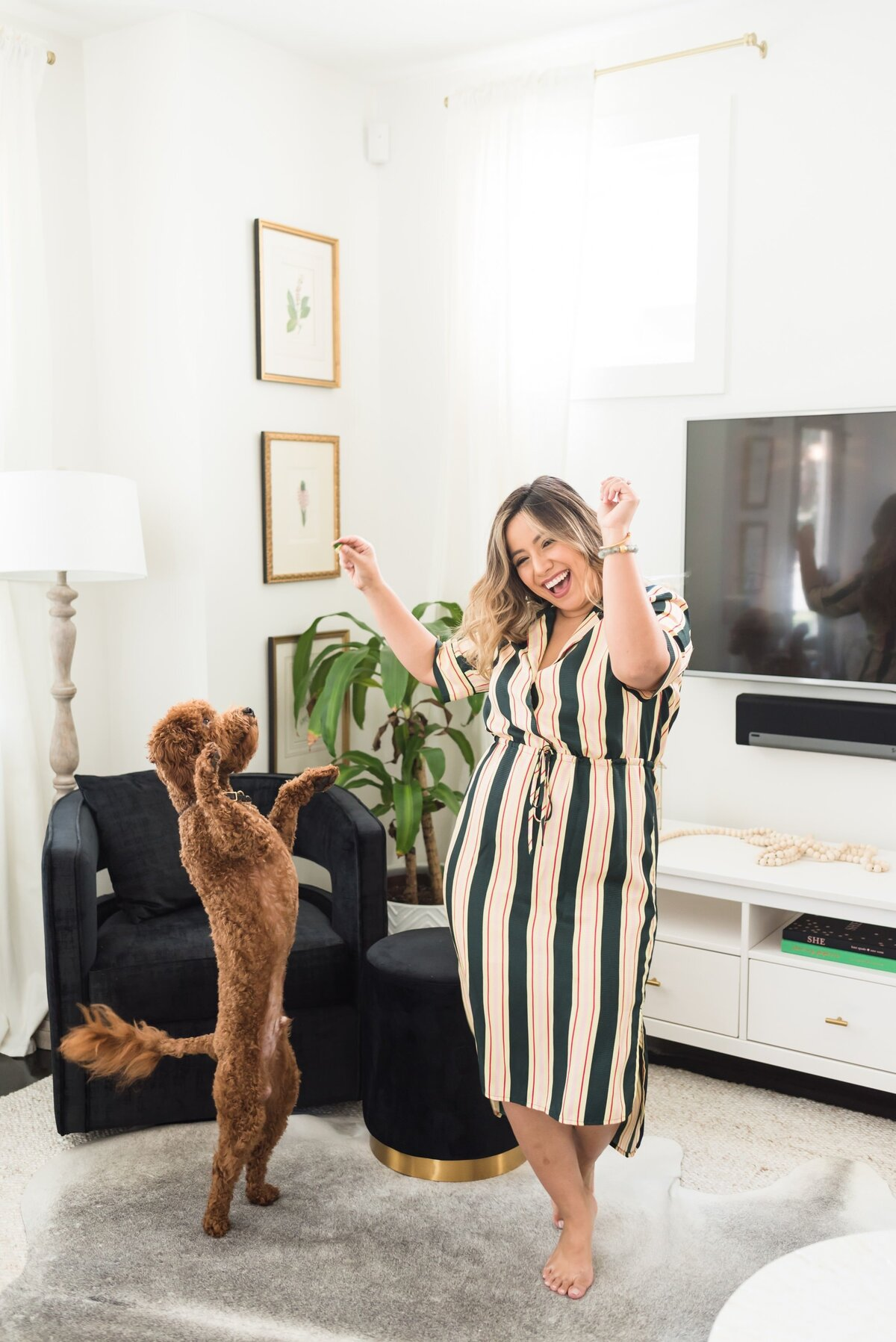 Latina business owner dancing with her dog in a living room for fun and casual personal brand photos