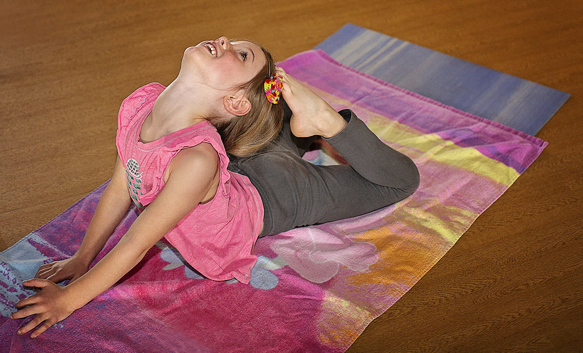 Young girl smiles while touching toes to her head in yoga class