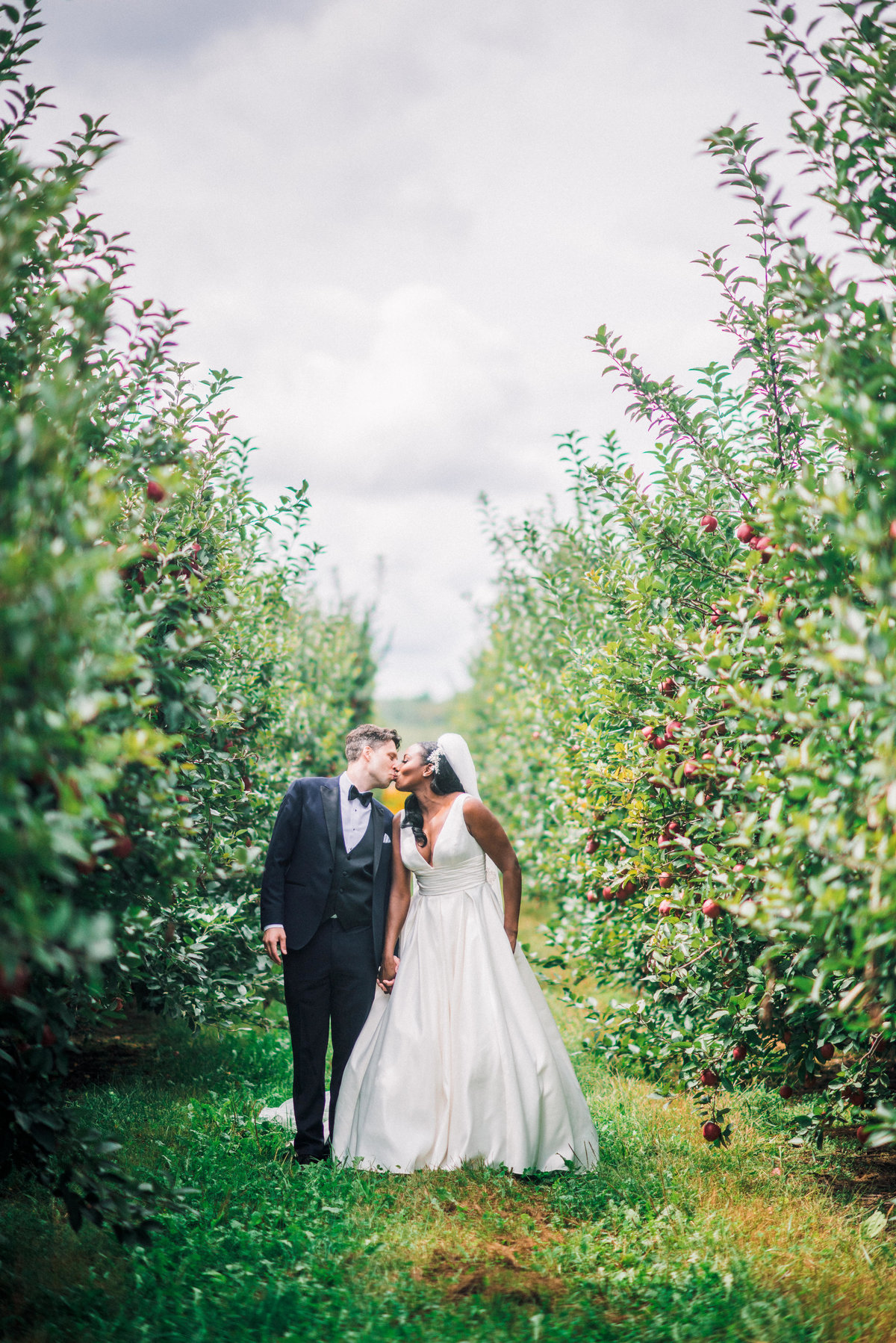 Bride and groom kiss in an apple orchard