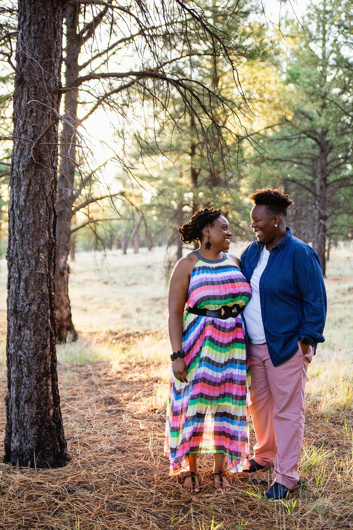 Same sex couple looking at each other during their sunrise engagement session in Flagstaff Arizona by PMA Photography.