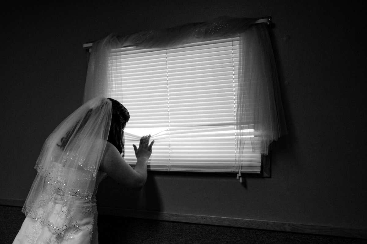 bride peeks at groom outside