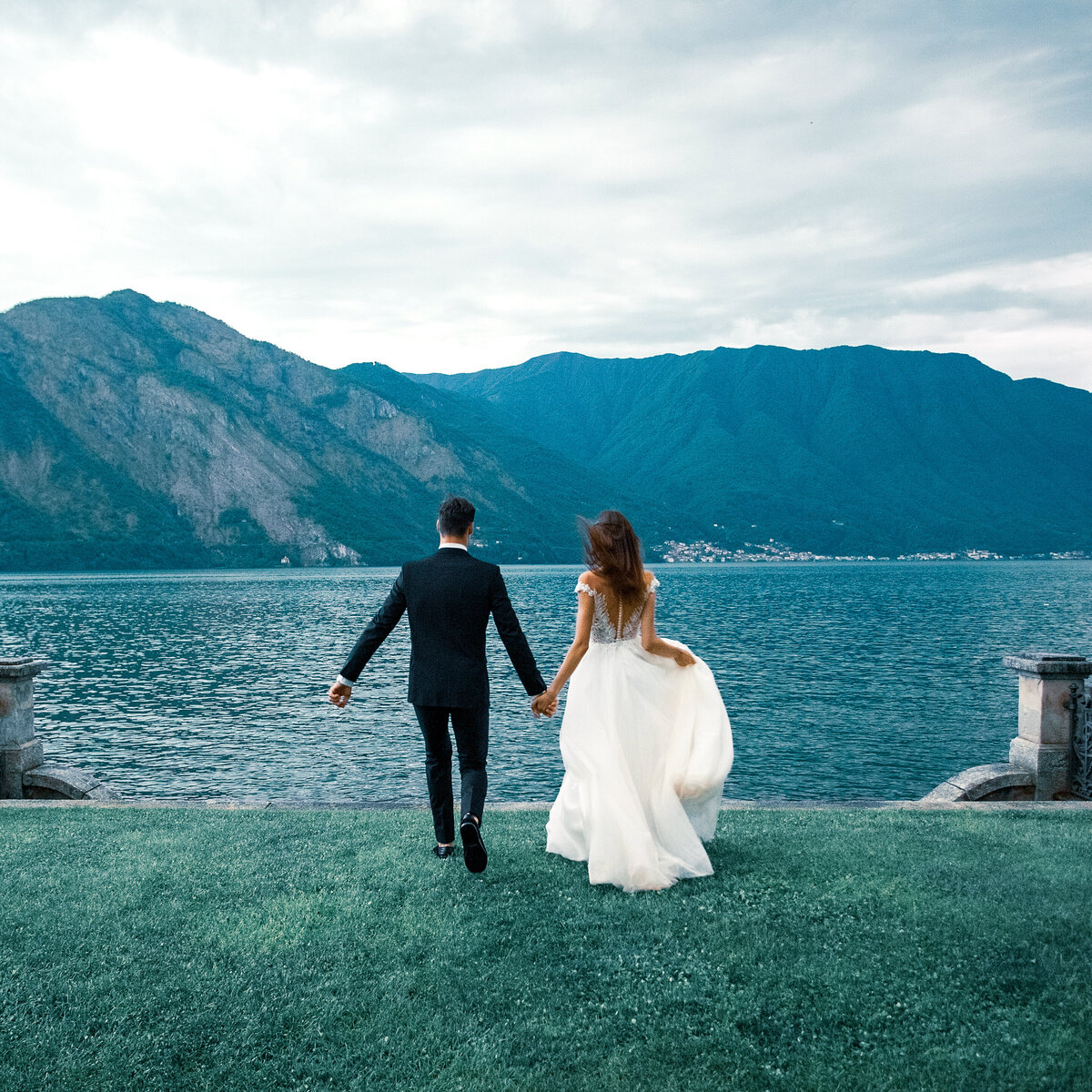 A wedding couple walking towards a lake in Lake Como, Italy on an overcast day/