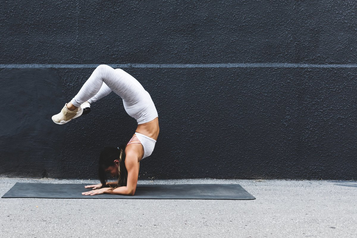 young-woman-doing-yoga-pose-against-black-wall