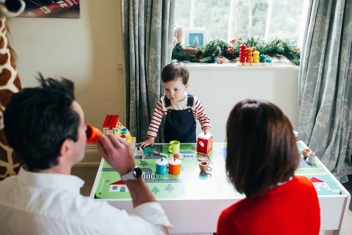 Natural photo of mum dad and toddler playing tea party