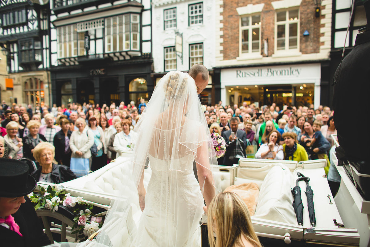chester grosvernor wedding photo of bride getting into horse drawn carriage with the crowds in street watching on