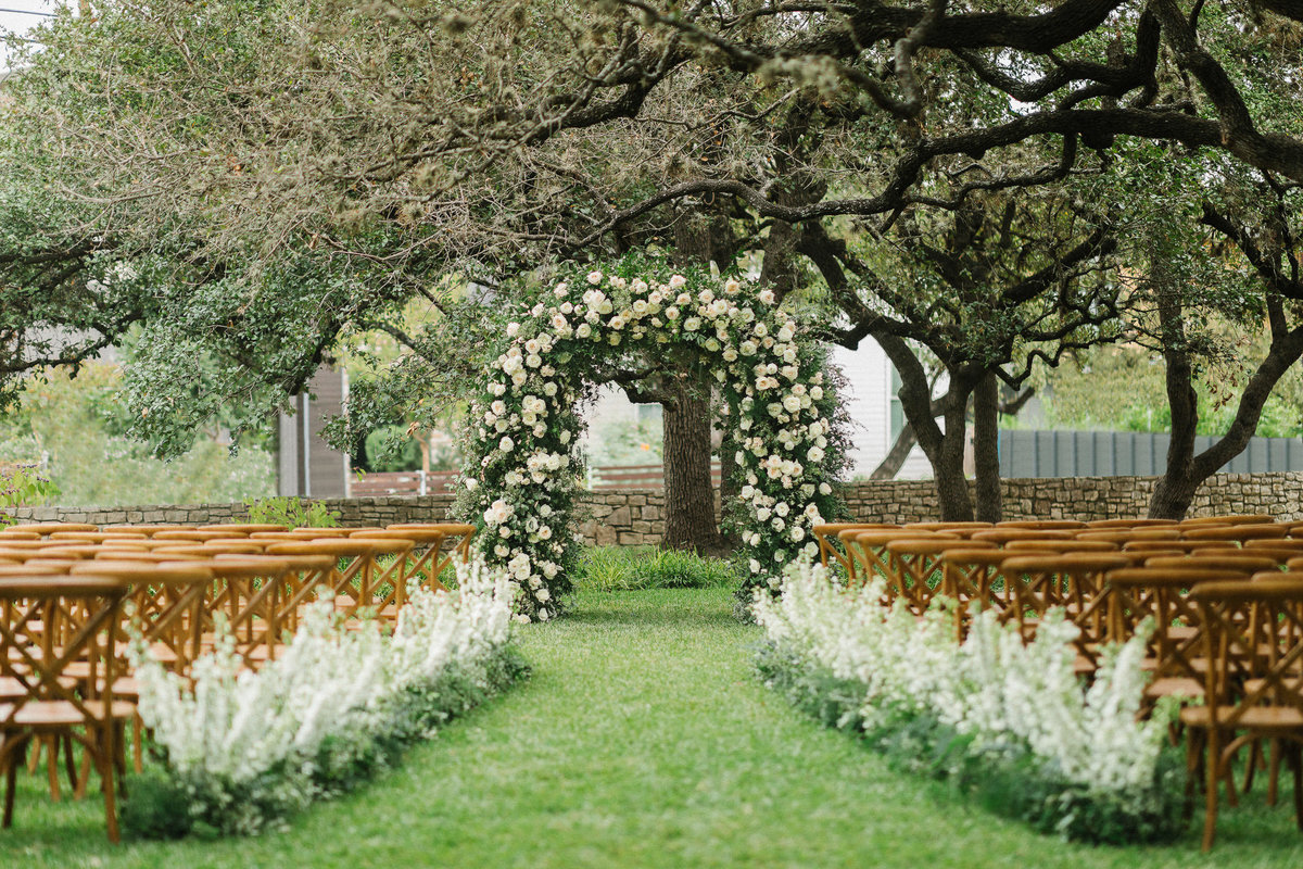 Wedding ceremony design altar Mattie's Austin Venue trees white flower arch brown chairs