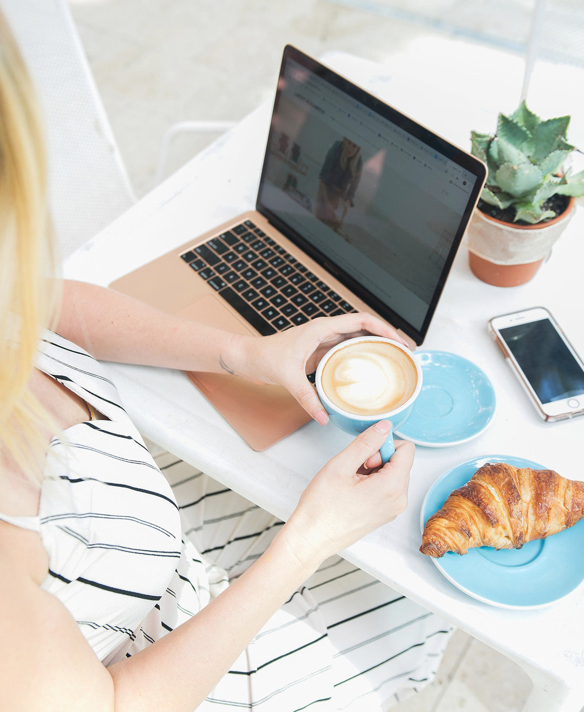 woman sitting at table  holding coffee cup with croissant and laptop