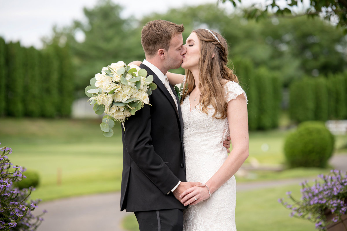 bride and groom kissing on the golf course at Willow Creek Golf and Country Club wedding photo