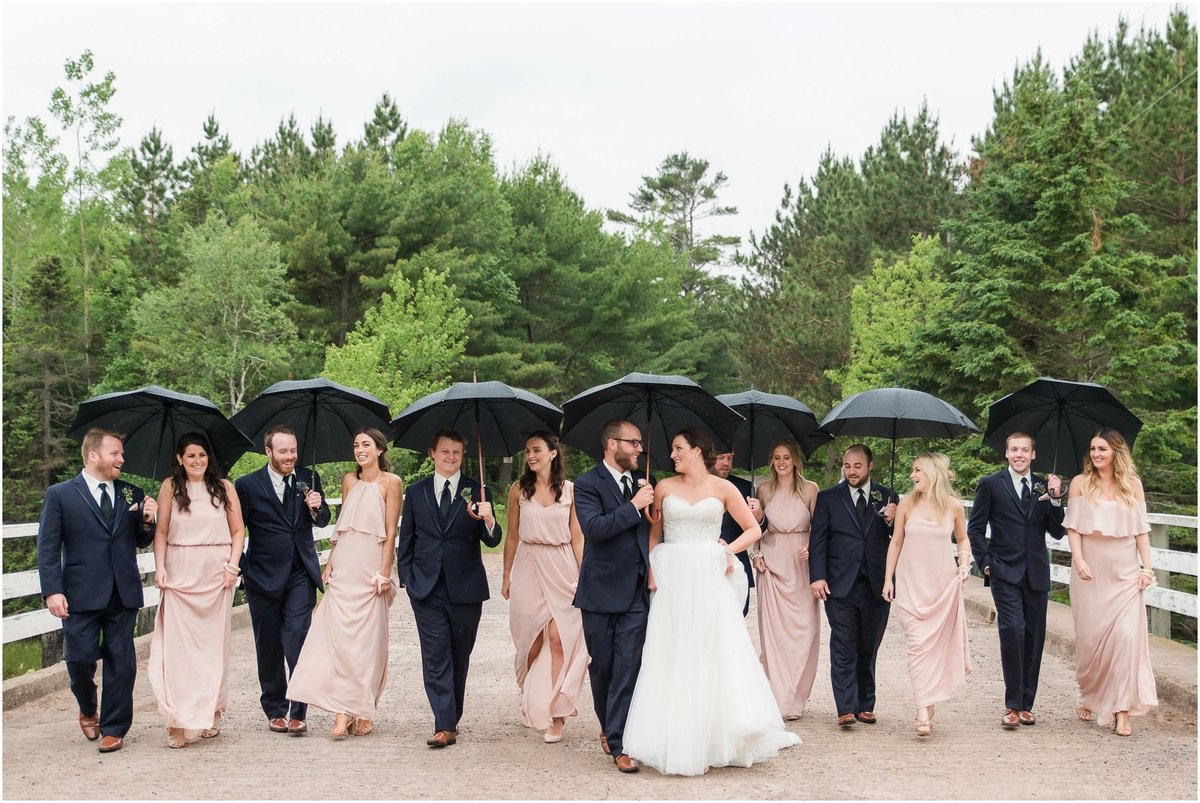 Wedding party, navy suits, blush dresses, umbrellas