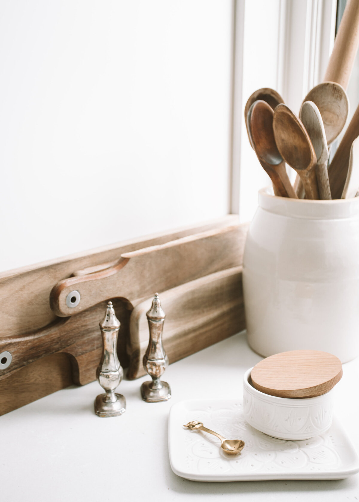 Wooden utensils are in a white ceramic pot next to some wooden chopping boards and silver salt and pepper shakers.