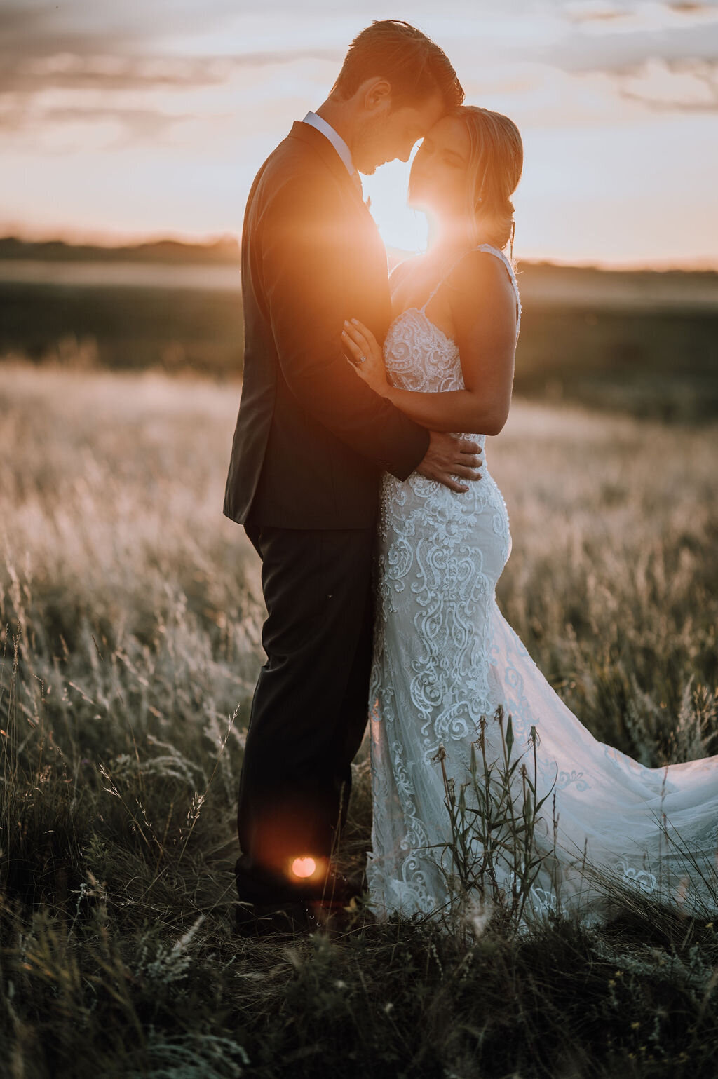 couple standing in a prairie field with the sun setting behind