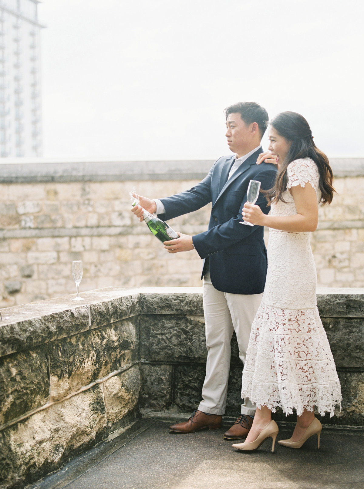 Couple popping champagne - engagement photos- Chateau Bellevue