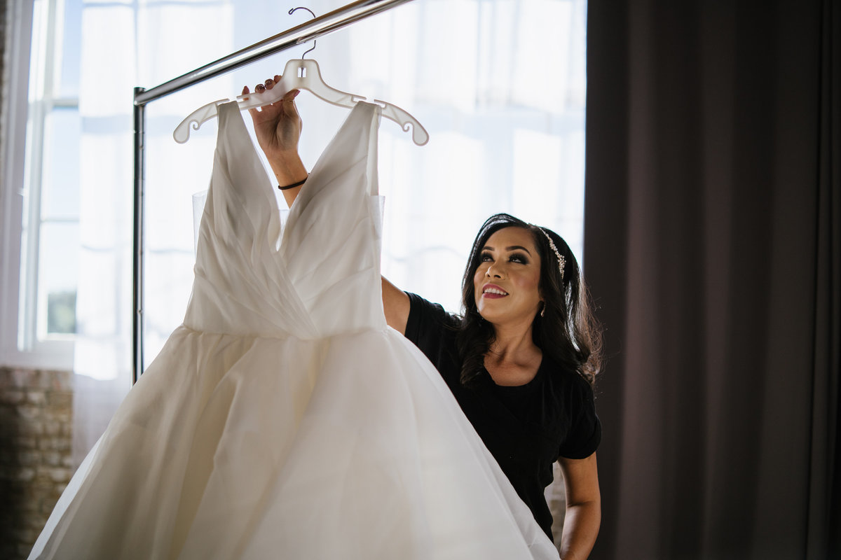Bride getting ready to put on bridal gown before wedding ceremony taking dress off rack.