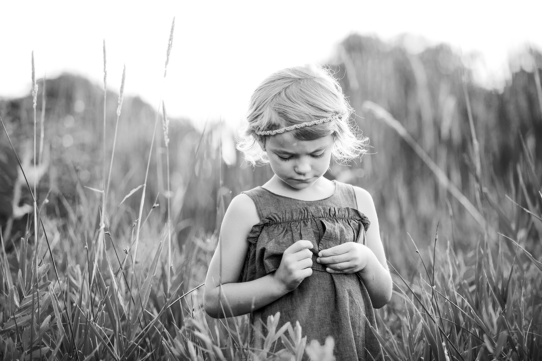 black and white photo of a girl looking at a piece of grass in her hand, light colored hair, photographed at River front park in billings montana next to the pond in spring