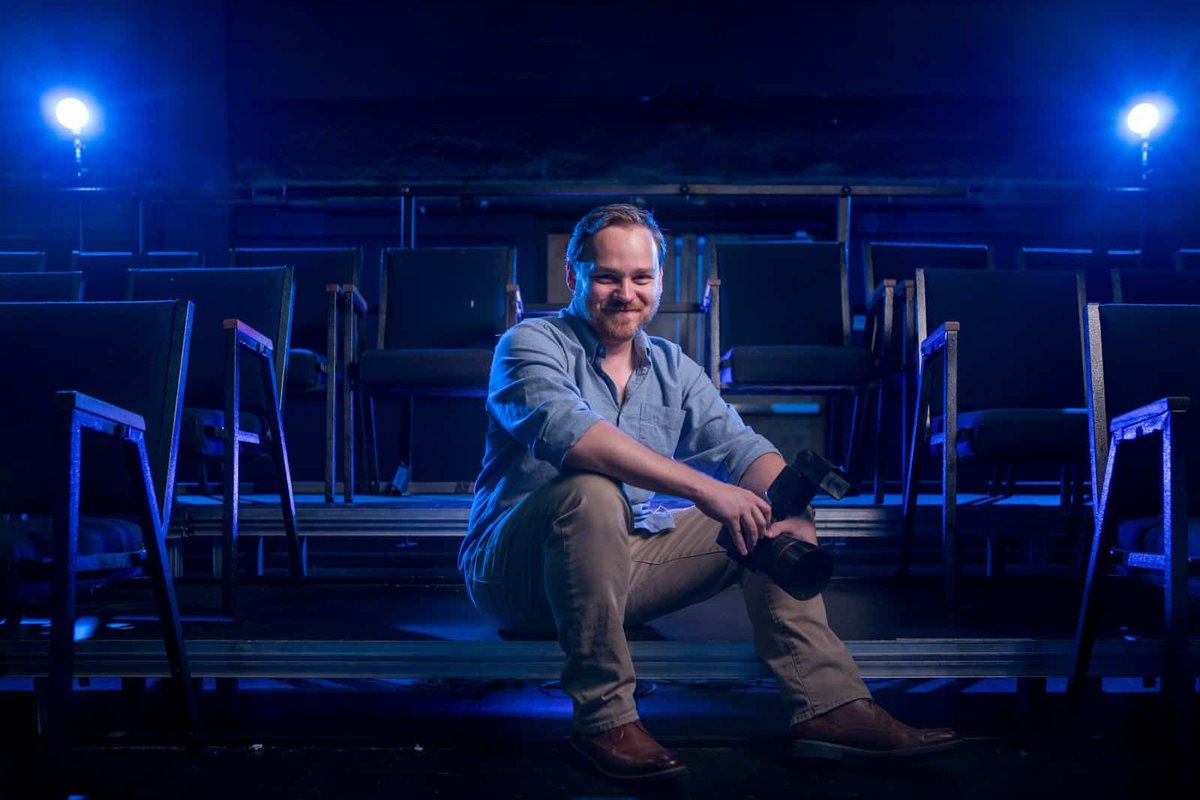 dramatic portrait of photographer sitting on Atlanta theater stage