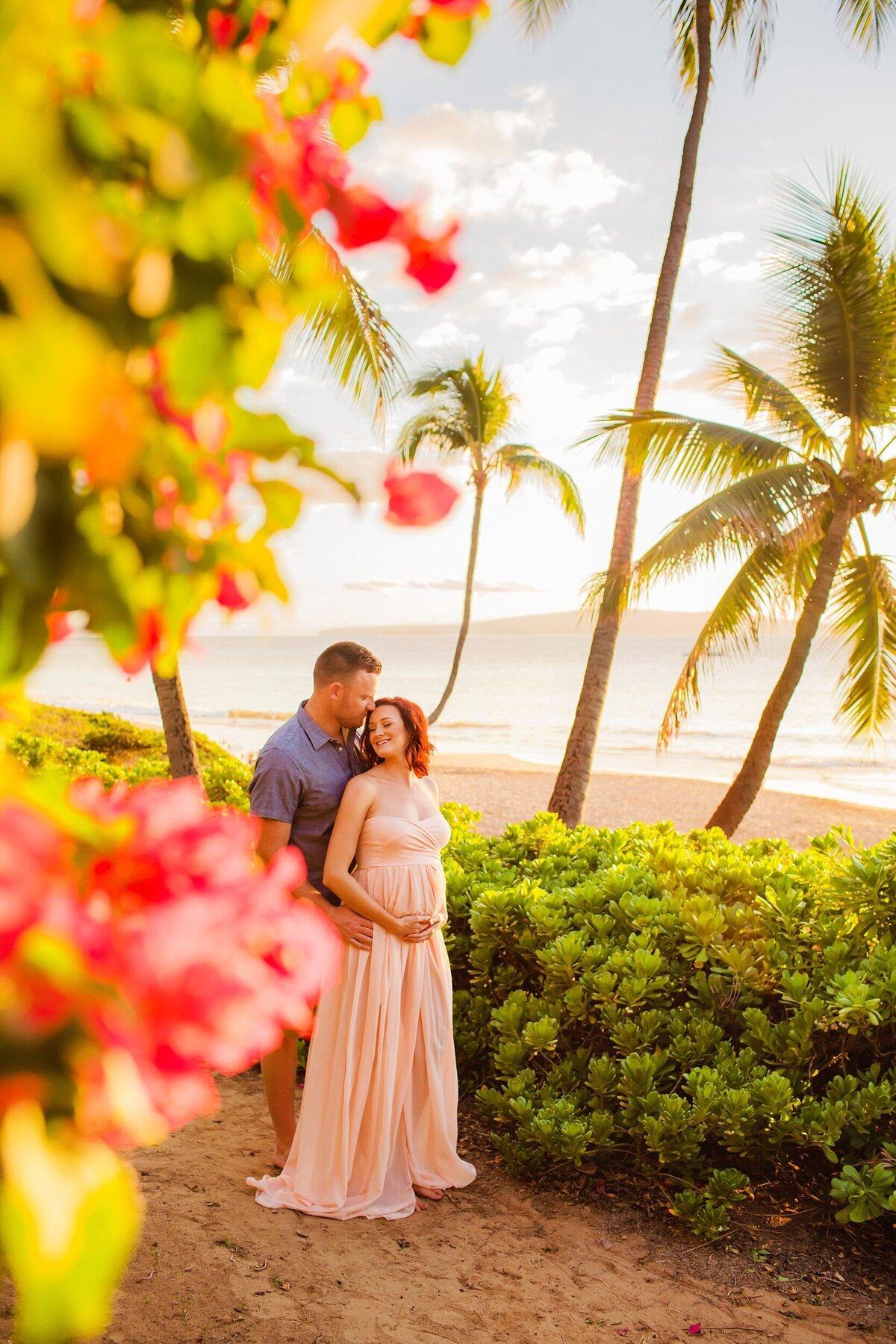 Vertical image of husband kissing pregnant wife framed by flowers on Maui