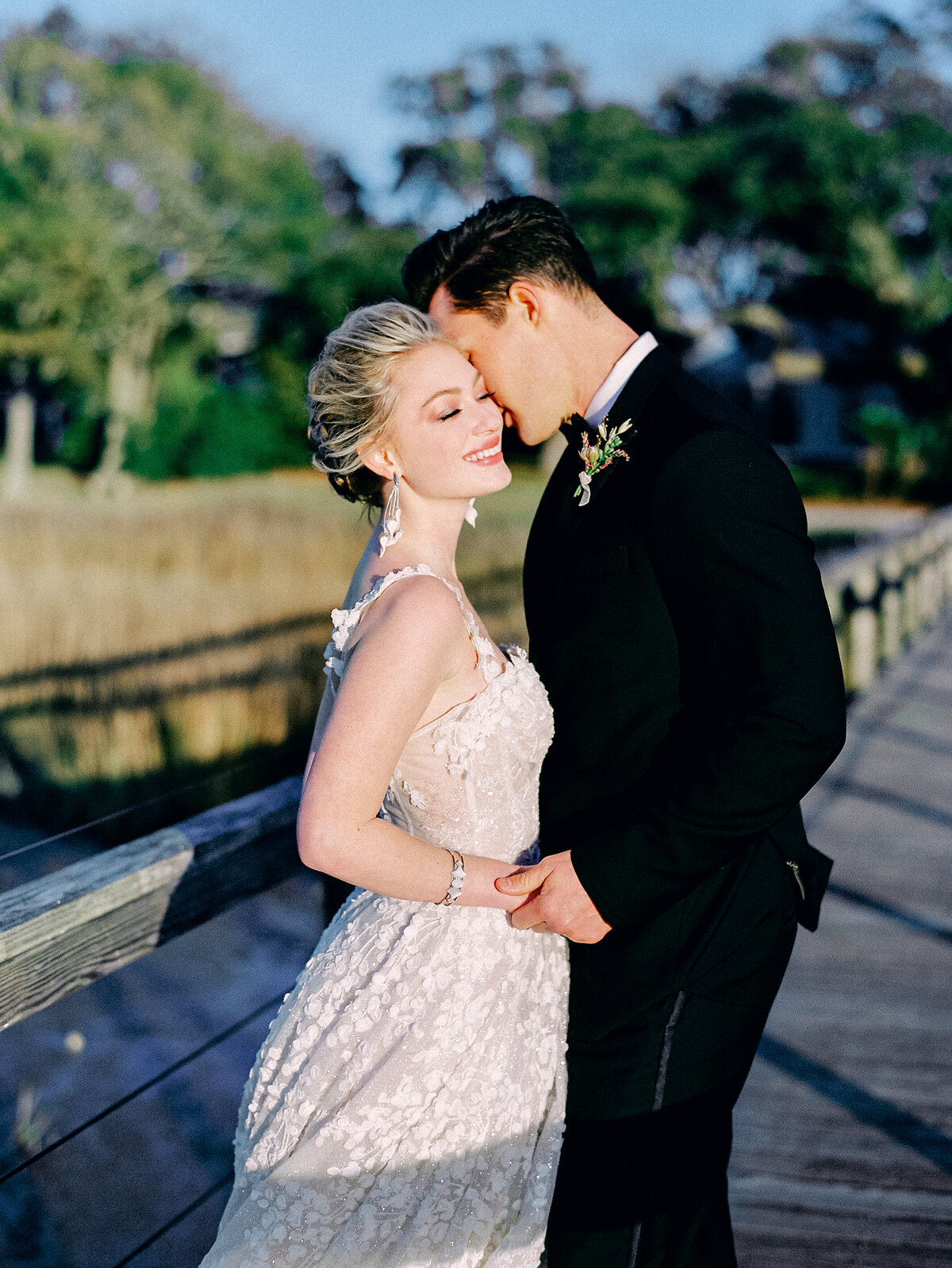 Bride and groom holding hands and embracing on wooden dock on river at Charleston Wedding