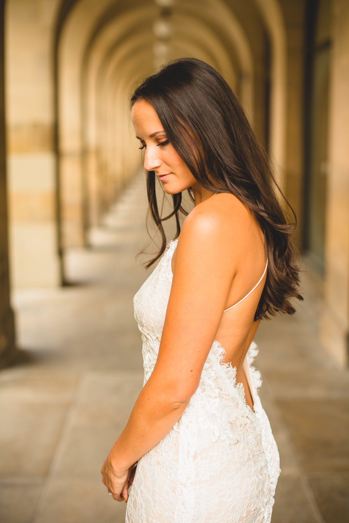 bride under archway in backless wedding dress