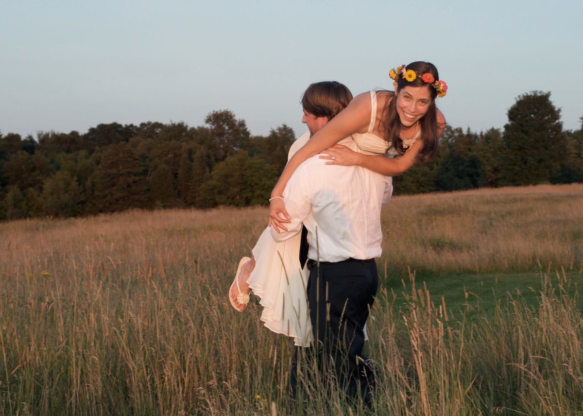 groom carrying bride over his shoulder in this sunset wedding photo in Morrisville, Vermont